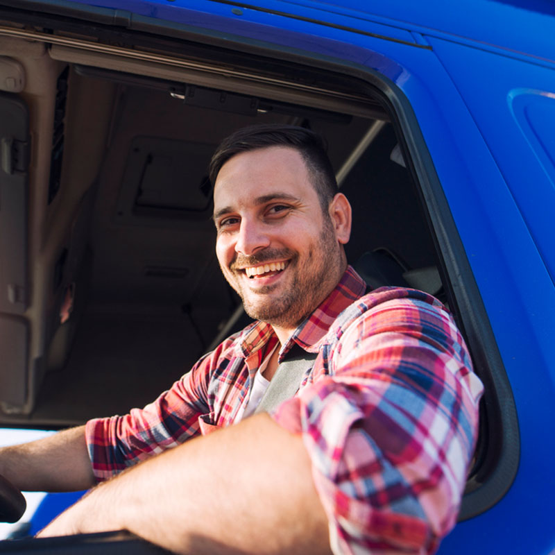 Happy truck driver smiling in his vehicle
