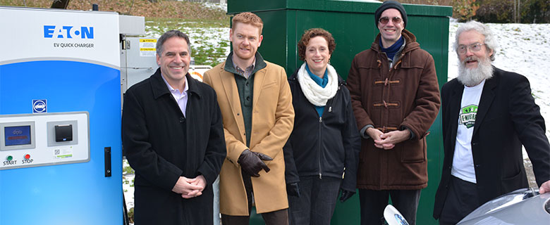 Mayor Darrell Mussatto standing beside the DC Fast Charge electric vehicle station with other community members in the City of North Vancouver