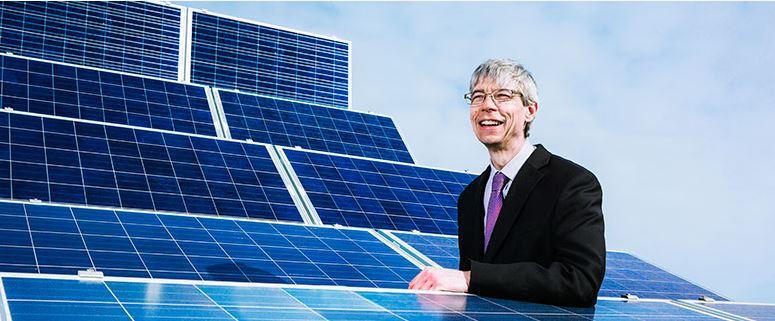 Mark standing among solar energy panels
