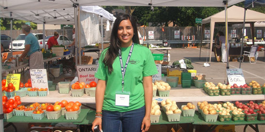 Woman in front of vegetable stand at farmers' market