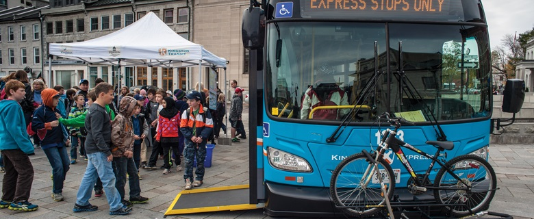 """Students getting on city bus. Bus sign states """"Express stops only."""" Bike secured on rack.  (Credit: City of Kingston)"""