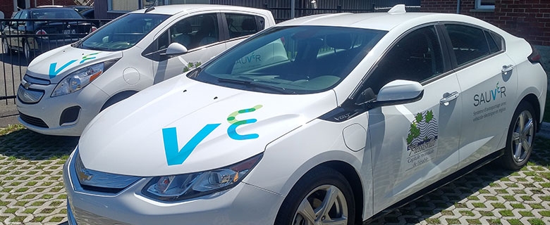 """Two electric vehicles, white. City of Plessisville logo on driver's door (City of Plessisville) and SAUVér project logo on rear door. The """"V"""" and """"E"""" logos appear on the hood"""
