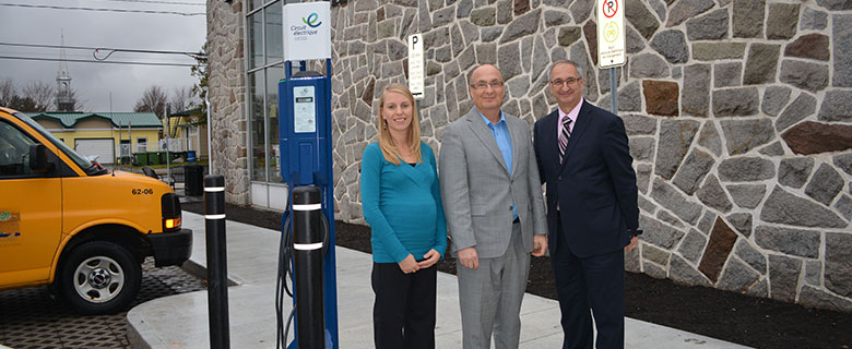 Justine Fecteau-Fortin, Director, Sustainable Development (left); Gaétan Blier, Councillor (centre); and Alain Desjardins (right), next to a charging station in front of Plessisville's City Hall.