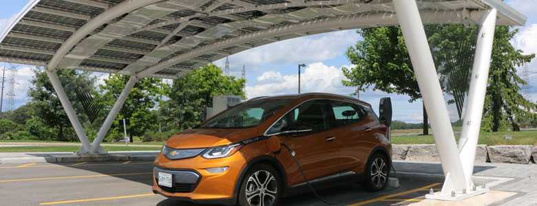 Carport with orange, four-door car while it is charging. (Credit: City of Ajax)