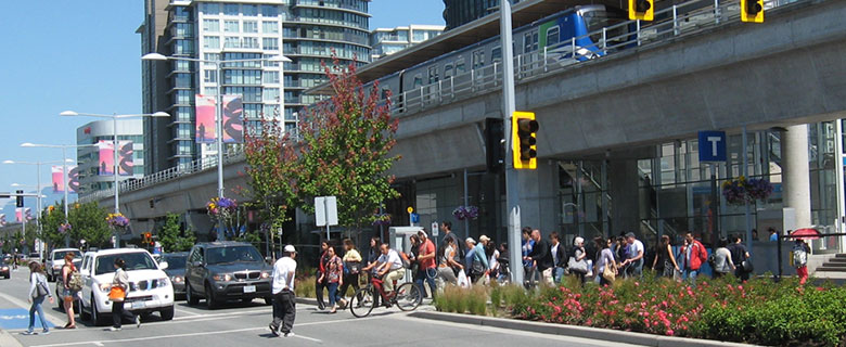 Active train in background (top right corner), with pedestrians crossing street (right to left) and bicycle lane with cyclists. (Credit: City of Richmond)