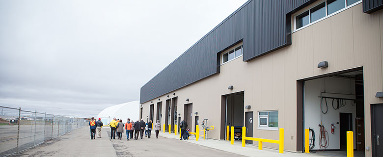 Spruce Grove solar wall, with group of people walking away. (Credit: City of Spruce Grove)