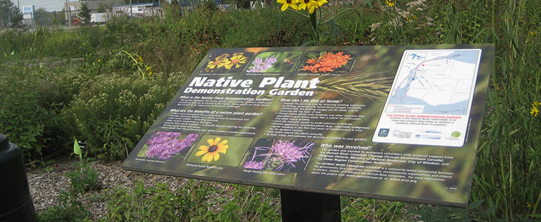 Plaque for the Native Plant Demonstration Garden explaining different fauna; image of garden behind.