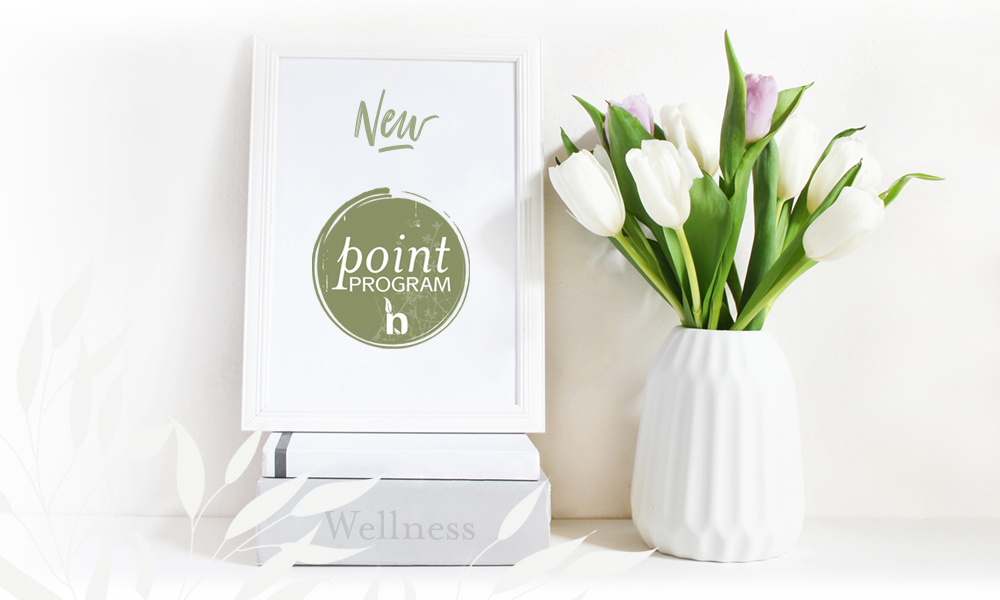 Spa points program logo on frame on a stack of books next to a vase filled with tulips