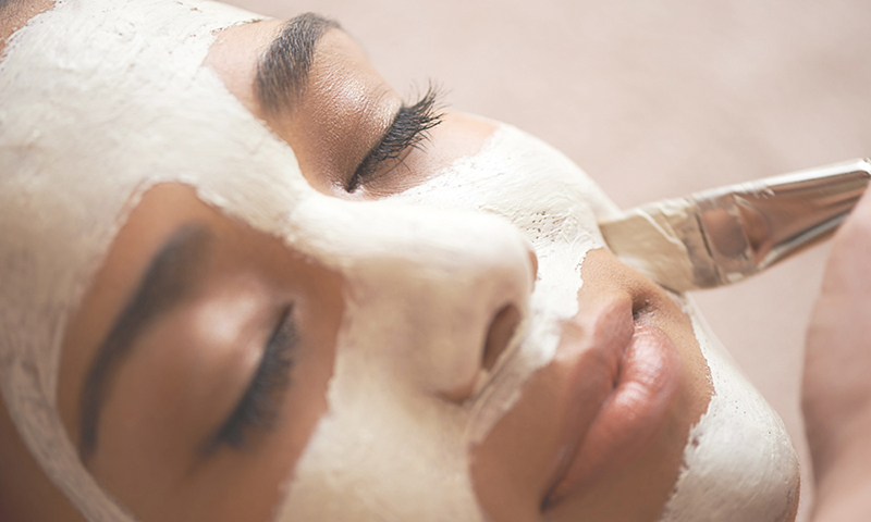 woman having a mask brushed onto her face