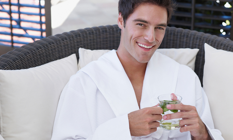 Male relaxing in a spa robe holding water infused with mint