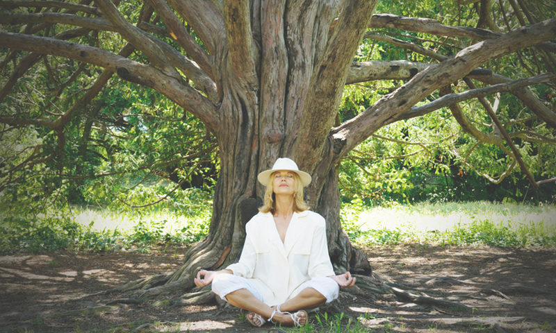 mature blonde woman wearing a hat meditating under a tree