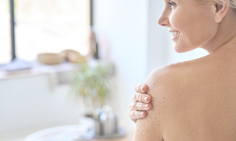 Back view of woman applying exfoliating scrub after shower.