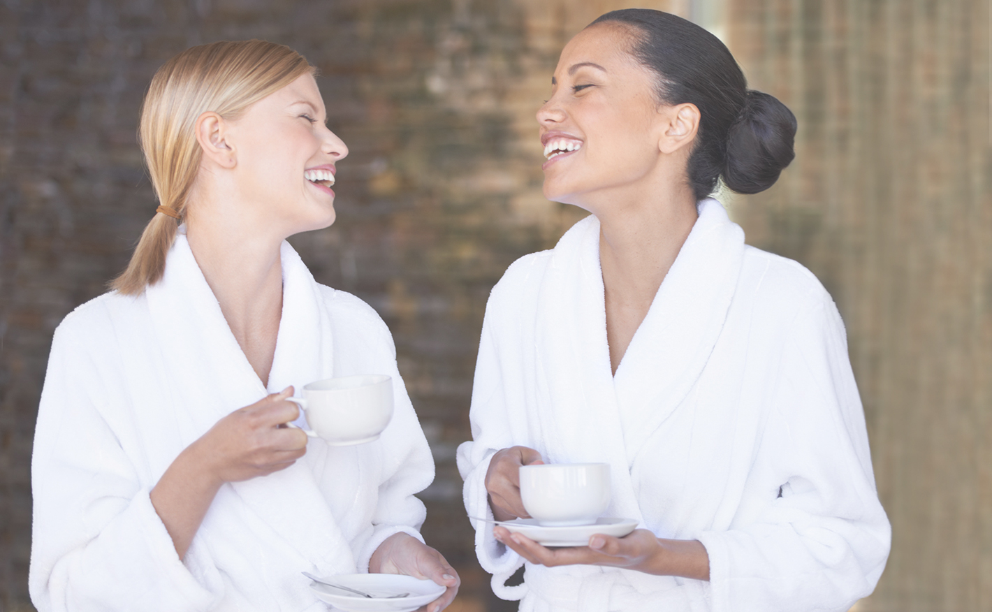 Two women wearing robes and enjoying tea at the spa.