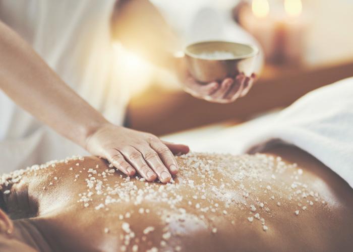Massage therapist exfoliating woman's back.