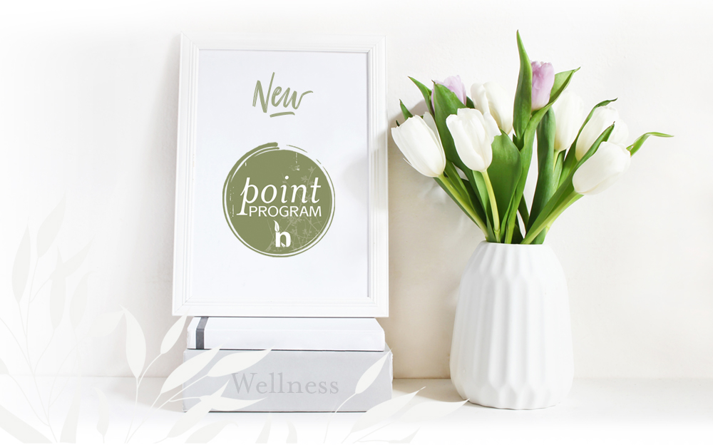 Natural Body Spa Point Program in a frame next to tulips in a vase.