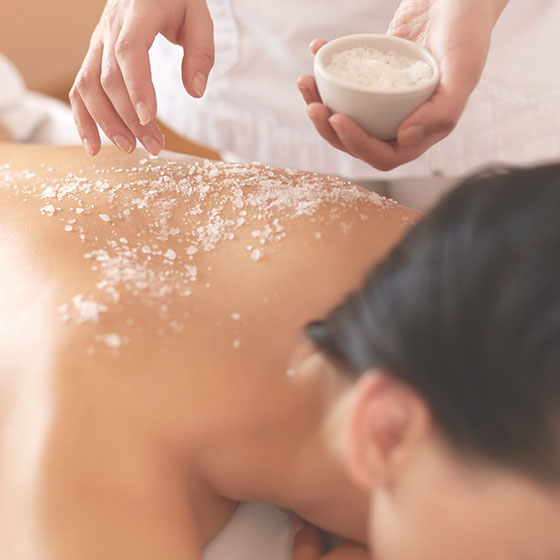 Woman receiving an exfoliation body treatment.