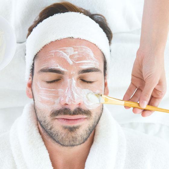 Man having a facial mask brushed onto his face.