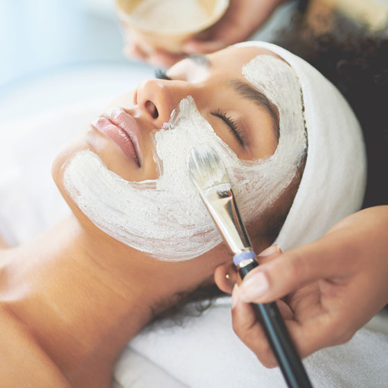 Woman relaxing during a facial service at the spa.