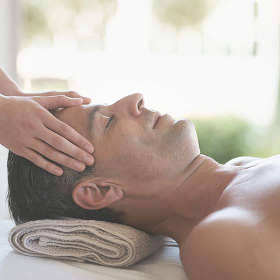 Mature male relaxing during a massage with hands on his forehead.
