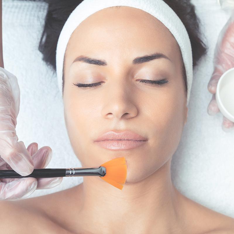 Woman receiving a facial peel.