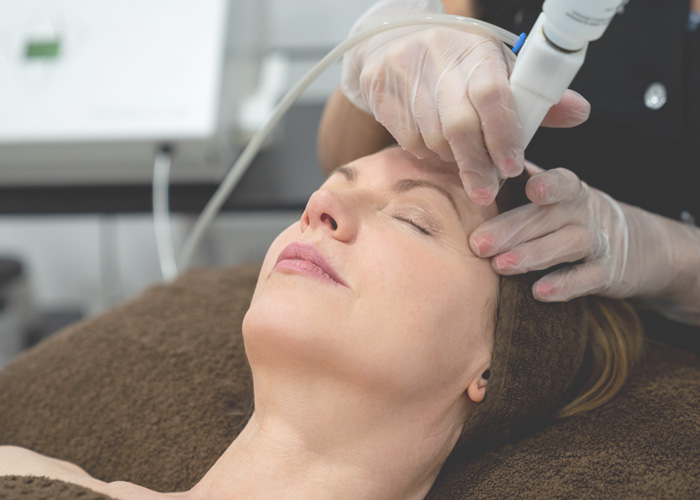 Mature woman receiving microdermabrasion treatment.