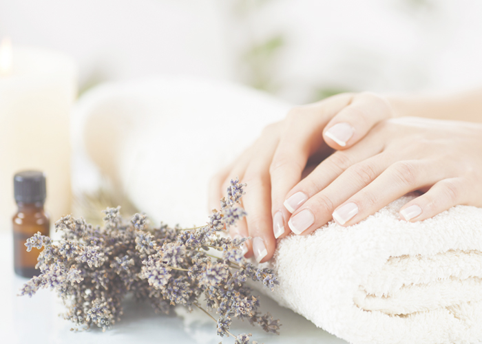 Freshly manicured hands next to lavender and essential oil bottle.