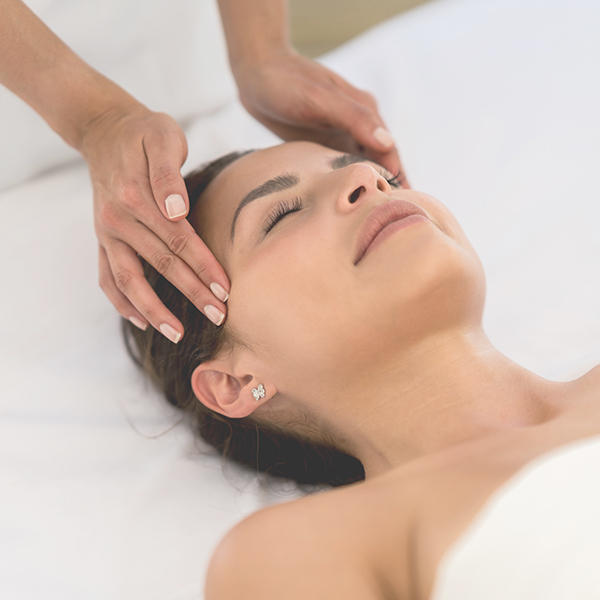 Woman relaxing at spa getting a facial.