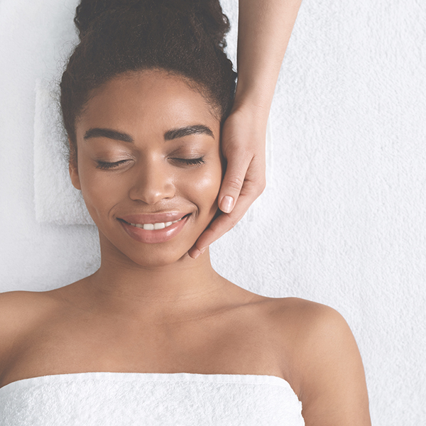 Joyful young woman  with closed eyes having face massage at spa.