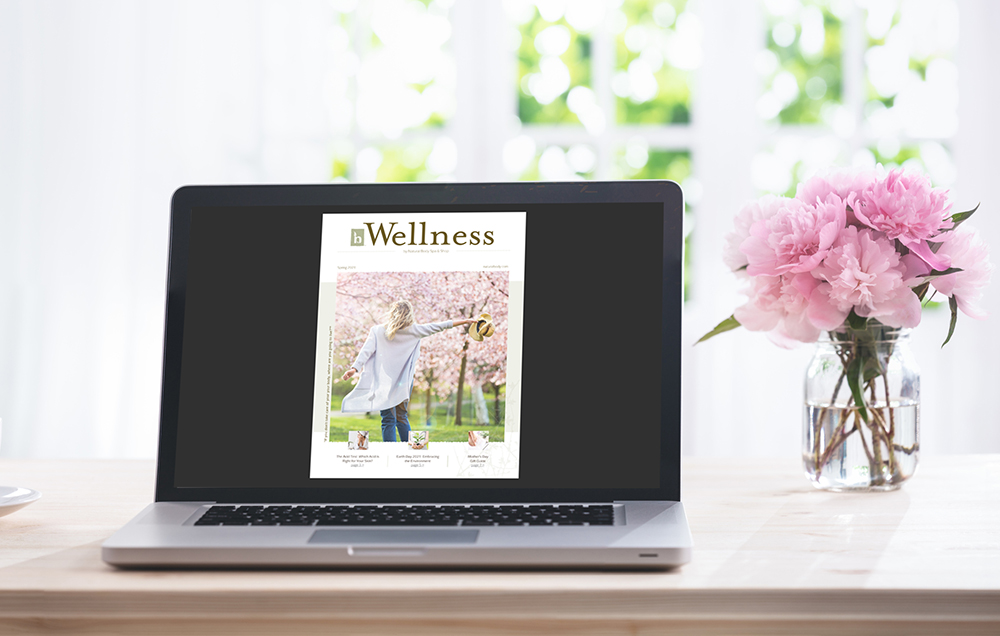 Spring Wellness Newsletter on laptop next to flowers.