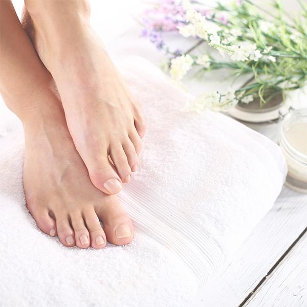 Freshly manicured feet resting on a towel