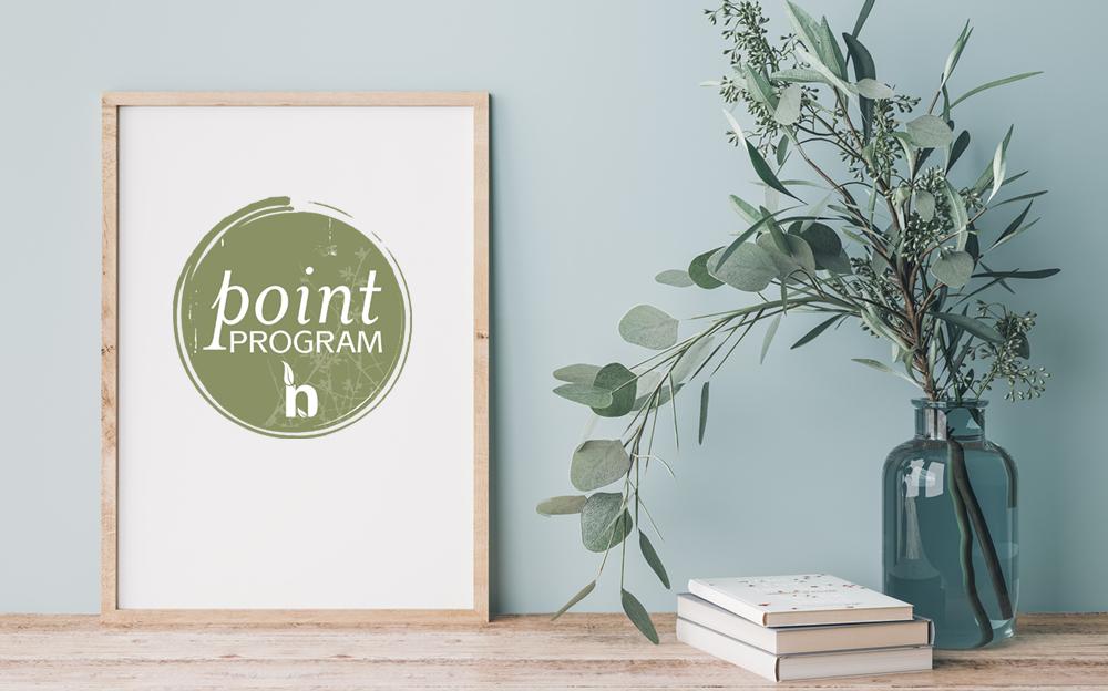 Point Program logo in frame next to eucalyptus in a vase