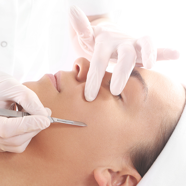 female being given a dermaplaning treatment