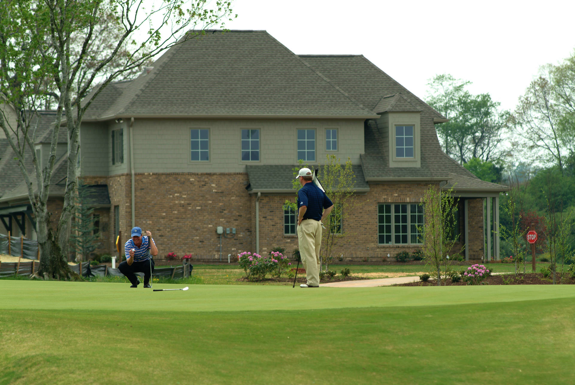 2 Men Golfing at Tennessee National with house in background