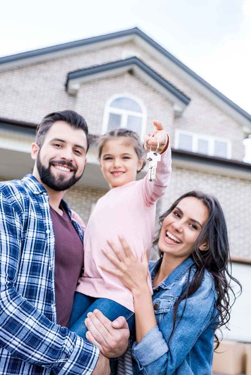 Familie mit Kind vor einem Haus mit Haustürschlüssel in der Hand