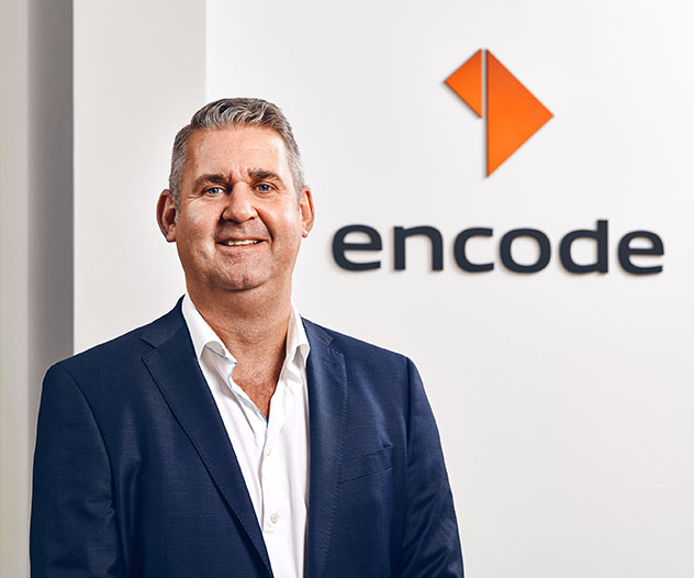 A guy in front of the Encode logo