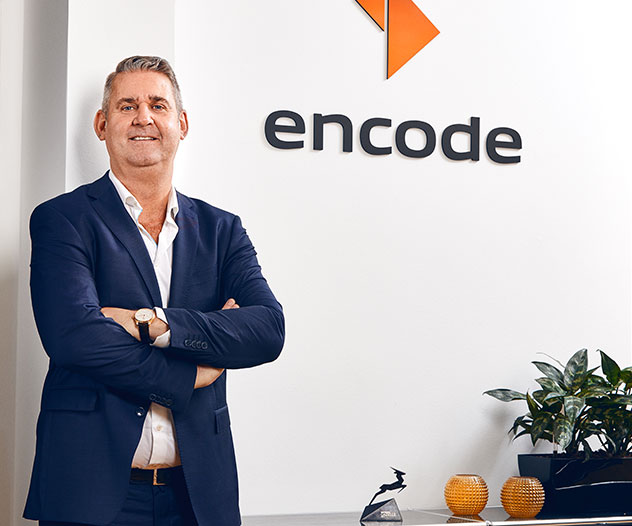A man in front of the Encode logo
