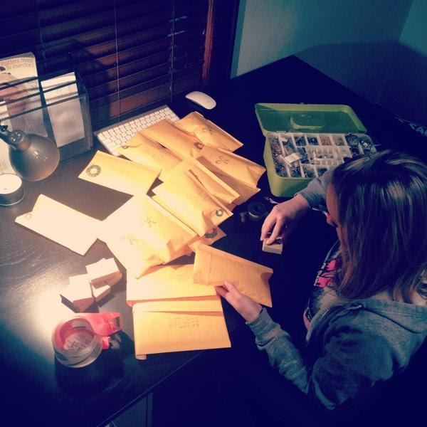 a young woman puts vintage-inspired jewelry in packages to mail them to customers
