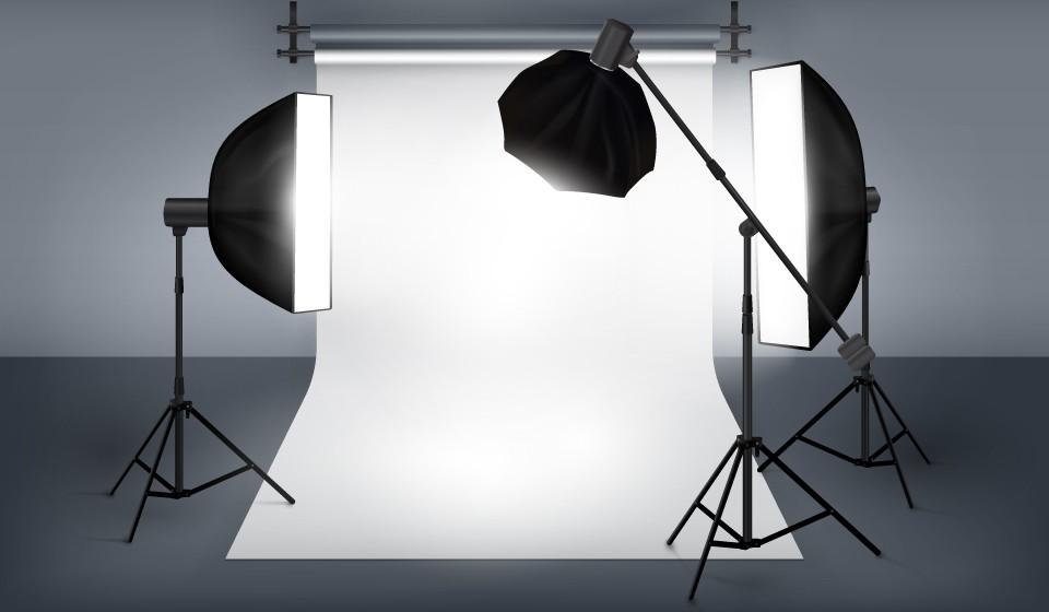 Studio photography setup with white sweep and three softbox lights