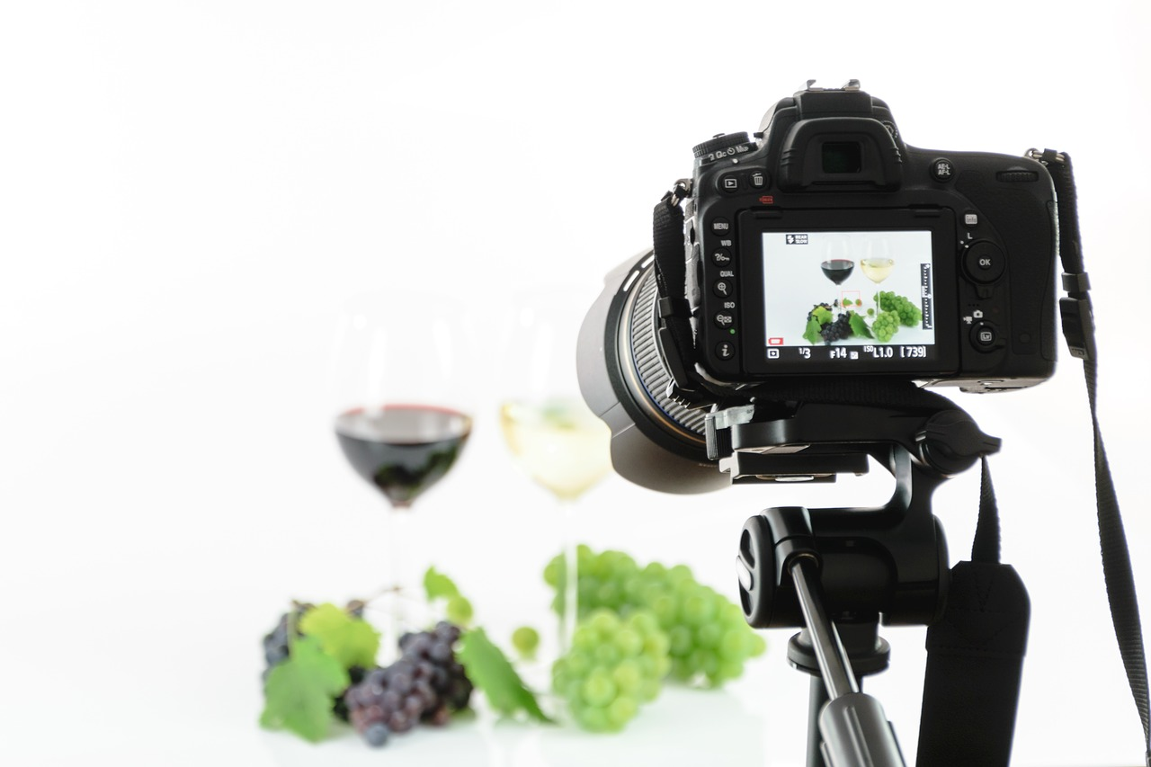 Professional camera shooting grapes and wine glasses against white background