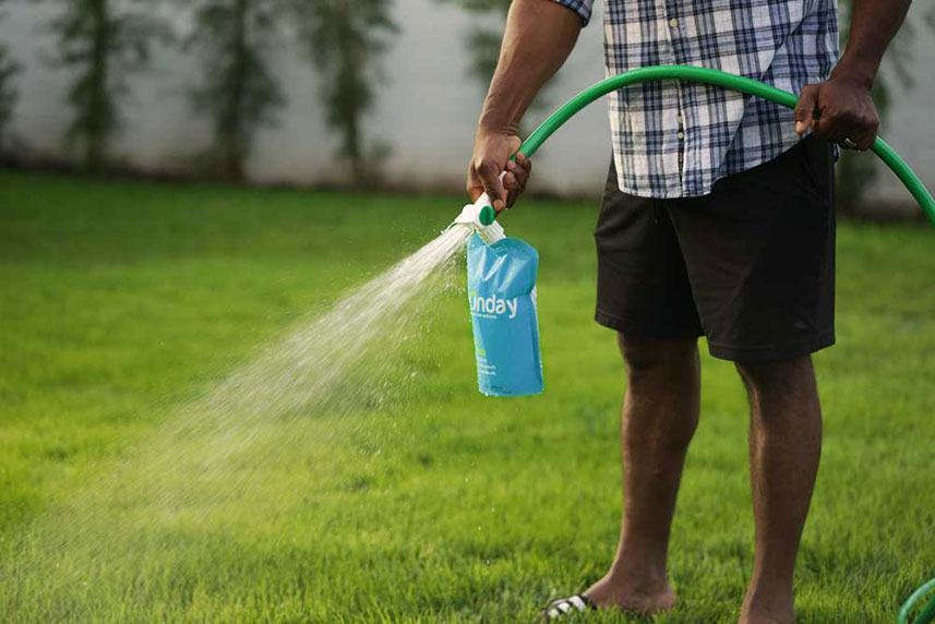 Sunday non-toxic fertilizer attached to a hose