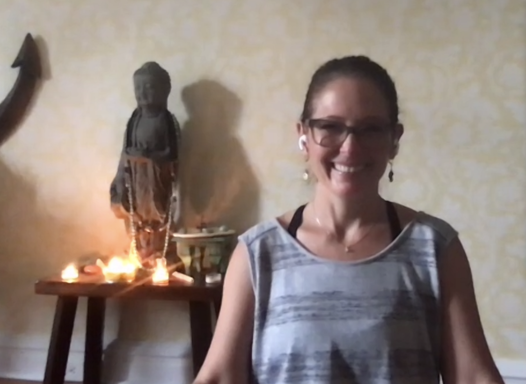 a woman surrounded by candles and a statue leading a guided meditation