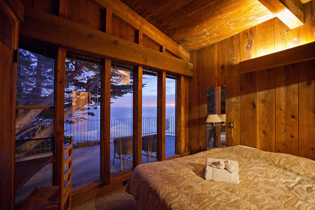 A wood paneled room containing a bed and chair, with a large window overlooking a small porch and the ocean
