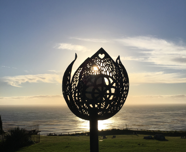 A photograph of a flower-shaped lantern in silhouette, with a green lawn, the blue sky, and the gray ocean in the background.