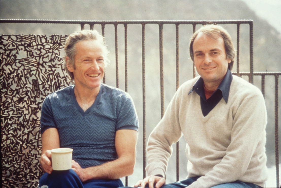 An older photography of two smiling men, both with light skin  and brown and gray hair, sitting outside. One man holds a coffee mug.