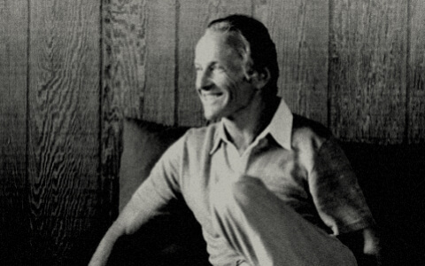 A black and white photograph of a smiling man wearing a collared shirt. He sits in front of a wood-paneled wall.