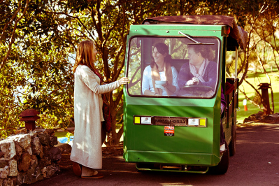 A photograph of a small green truck on a path under trees. Two people sit inside. Next to the truck stands a woman in a long white dress.