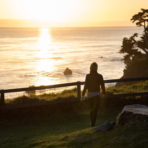 An Esalen guest enjoys sunset from the edge of the Pacific Ocean at Esalen.