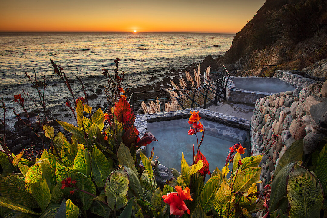 The Pacific ocean at sunset makes for a dramatic view from two of the large, communal tubs at the Esalen Baths.