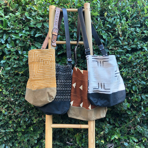 Assorted Jenna Bee handmade African Mudcloth tote bags hanging on a ladder