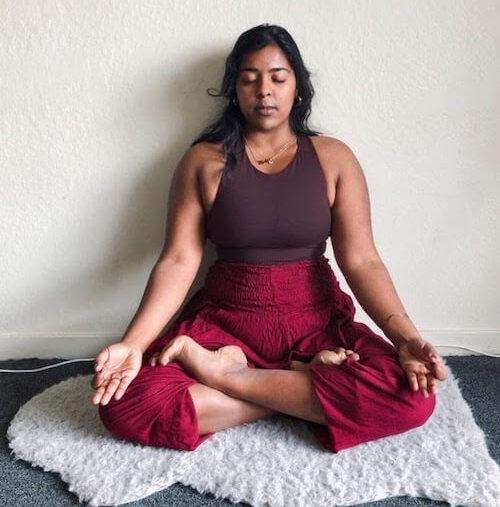 Divya Bala, yoga teacher, seated in her own, ancestral practice in Sukhasana (Easy Pose)
